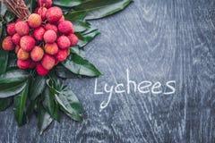 Nya organiska litchiplommonfrukt och litchiplommonsidor på ett lantligt trä royaltyfria foton