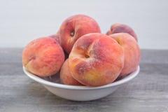 Nya organiska persikor i den vita bunken, på trätabellen royaltyfri bild