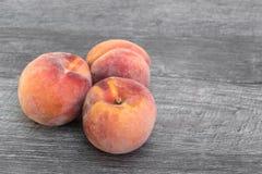 Nya organiska persikor på träbakgrund arkivfoton