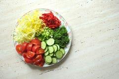 Nya organiska skivade grönsaker på den vita plattan på trätabellen Bästa sikt, lekmanna- lägenhet Royaltyfri Foto