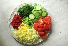 Nya organiska skivade grönsaker på den vita plattan på trätabellen Bästa sikt, lekmanna- lägenhet Royaltyfri Fotografi
