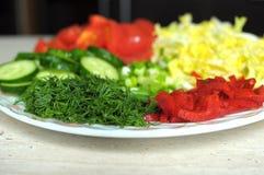 Nya organiska skivade grönsaker på den vita plattan på trätabellen Nära övre, selektivt fokuserar Arkivfoton