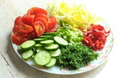 Nya organiska skivade grönsaker på den vita plattan på trätabellen Nära övre, selektivt fokuserar Arkivbild