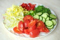 Nya organiska skivade grönsaker på den vita plattan på trätabellen Nära övre, selektivt fokuserar Royaltyfri Fotografi