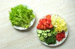 Nya organiska skivade grönsaker på två vita plattor på trätabellen Bästa sikt, lekmanna- lägenhet Royaltyfri Foto