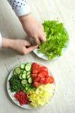 Nya organiska skivade grönsaker på två vita plattor på trätabellen Process av matlagning Fotografering för Bildbyråer