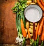 Nya organiska trädgårds- grönsaker runt om den tomma gamla matlagningpannan på träbakgrund, bästa sikt Royaltyfri Bild