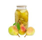 Nya päron Bartlett och på burk päron i den glass kruset Arkivbild
