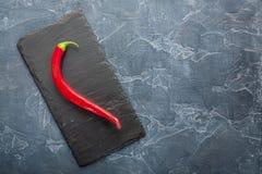 Nya peppar för röd chili på en mörk sten med uttrycksfull textur Arkivbild