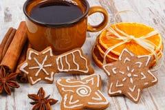 Nya pepparkaka, kopp kaffe och kryddor på gammal träbakgrund, jultid royaltyfri foto