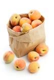 Nya persikor i den isolerade pappers- påsen Fotografering för Bildbyråer