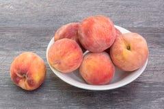 Nya persikor i den vita bunken, på träbakgrund royaltyfria foton