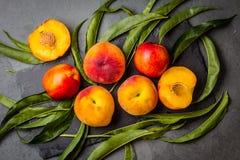 Nya persikor på den svarta stenen pläterar, grå färger kritiserar bakgrund Arkivfoto