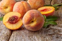 Nya persikor på träbakgrund Arkivbilder