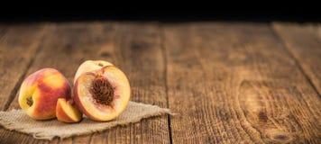 Nya persikor på träbakgrund; selektiv fokus Royaltyfri Bild