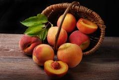 Nya persikor som faller ut ur en korg Royaltyfria Bilder