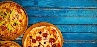 Nya pizza på den blåa trätabellen Arkivbild