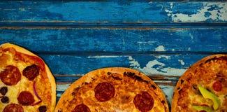 Nya pizza på den blått red ut tabellen Arkivfoton