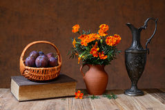 Nya plommoner i en vide- korg och en flowershttp://www dreamstime com/fresh-oranges-and-dried-flowers-in-a-vase-image42545715 Arkivfoton