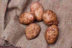 Nya potatisar på säckväv på trätabellen, bästa sikt Arkivbild