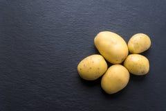 Nya potatisar på svart Arkivfoto