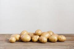 Nya potatisar på trätabellen Royaltyfria Bilder
