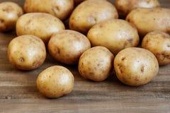 Nya potatisar på trätabellen Royaltyfri Fotografi