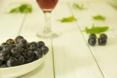 Nya purpurfärgade druvor på plattan arkivbilder