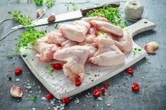 Nya rå fega vingar på en vit skärbräda med timjan, chili som är salt, peppar, vitlök Royaltyfri Foto