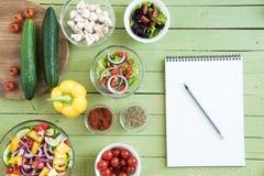 Nya rå grönsaker och sallader i bunkar och tom anteckningsbok med blyertspennan på trätabellen Royaltyfri Fotografi