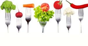 Nya rå grönsaker på gafflar på vit bakgrund Arkivfoton