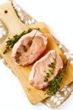 Nya rå grisköttbiffar på skärbräda Arkivfoton