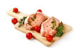 Nya rå grisköttbiffar på skärbräda Arkivbild