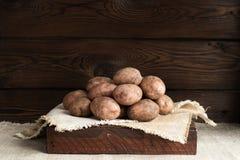 Nya rå potatisar i en mörk träask På linnekanfas Mot bakgrunden av ett gammalt mörkt bränt träbräde arkivbild