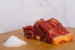 Nya rå skivor för nötköttköttbiff på träklippt bräde över vit bakgrund royaltyfri foto