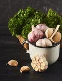 Nya rå vitlökkulor och kryddnejlikor i vit kopp- och gräsplansalade Royaltyfri Bild