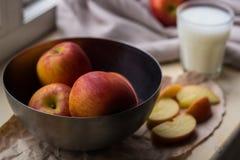 Nya röda äpplen i ett stilfullt järn besegrar att ligga på en vit fönsterfönsterbräda Apple skivor och ett exponeringsglas av mjö royaltyfria bilder