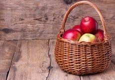 Nya röda äpplen i korg över träbakgrund Royaltyfri Foto