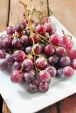 Nya röda druvor på den vita maträtten och trätabellen arkivbild