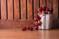 Nya röda druvor på en gammal wood tabell fotografering för bildbyråer