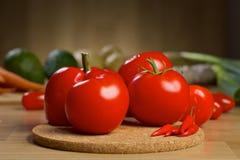Nya röda grönsaker på ett träbräde Arkivbild