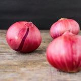 Nya röda lökar på en träbakgrund Fotografering för Bildbyråer