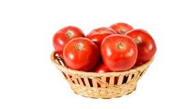 Nya röda tomater i korgen som isoleras på vit Selektivt fokusera arkivfoton