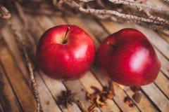 Nya röda två kopplar ihop äpplet på brunt lantligt bräde Royaltyfri Bild