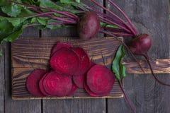 Nya rödbetor med sidor på den wood tabellen Helhet och klippta rödbetor Royaltyfri Fotografi