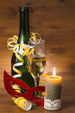 Nya år dagstilleben med champagneflaskan, exponeringsglas och den brännande stearinljuset Royaltyfri Bild