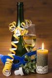 Nya år dagstilleben med champagneflaskan, exponeringsglas och den brännande stearinljuset Royaltyfri Foto