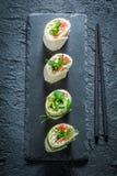 Nya rullar med laxen, ost och grönsaker för ett mellanmål Arkivfoto