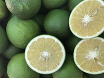 Nya söta apelsiner och några klippte i en halva Royaltyfri Foto