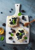 Nya söta Blackberry, blåbärbruschetta, rostat bröd med keso, honung i ett vitt bräde royaltyfri bild